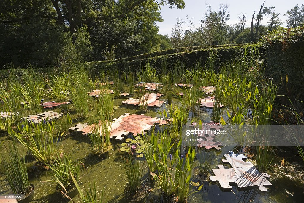Chateau garden, pond with floating puzzle pieces.