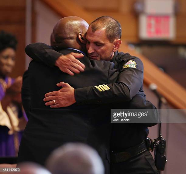 Chattanooga Chief of Police Fred Fletcher is hugged as he prepares to speak during an Interfaith Prayer Vigil at Olivet Baptist Church to honor the...