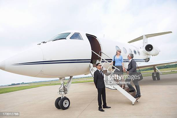 Chauffeur assisting mature couple as they board luxurious private jet