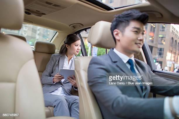 Chauffeur driving car for a businesswoman