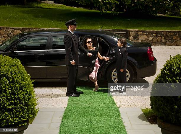 Chauffeur helping wealthy woman out of car