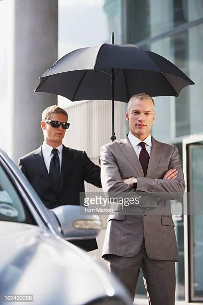 Chauffeur tenant un parapluie pour homme d'affaires