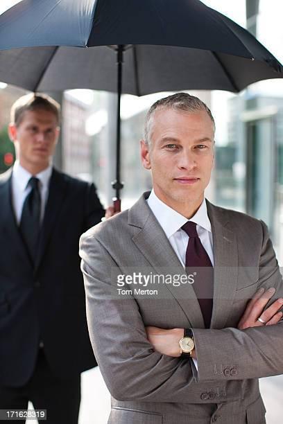 Chauffeur holding umbrella for businessman