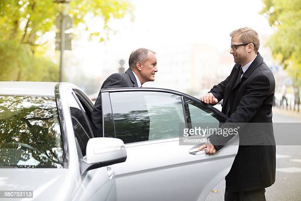 Chauffeur opening car door for businessman getting out