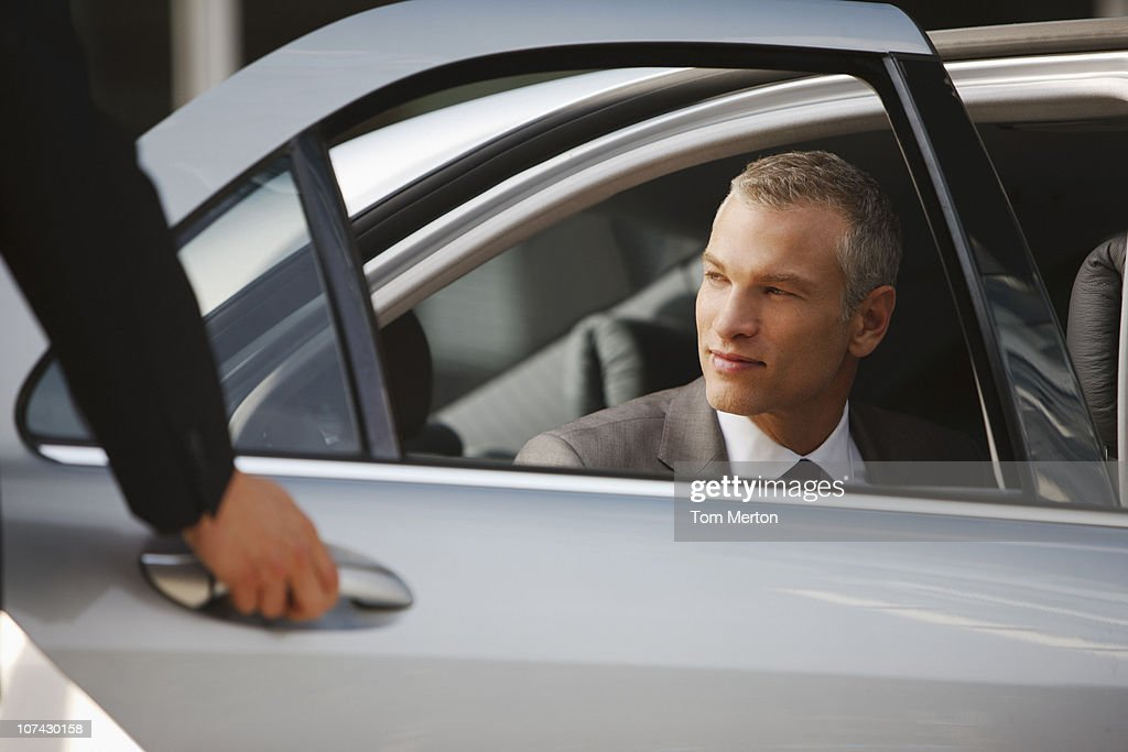 Chauffeur opening car door for businessman : Stock Photo