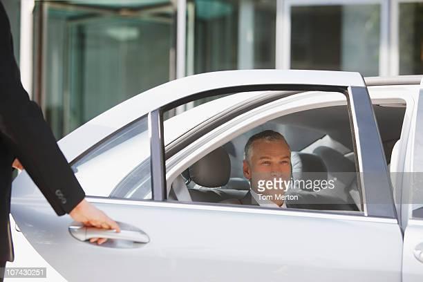 Chauffeur opening car door for businessman
