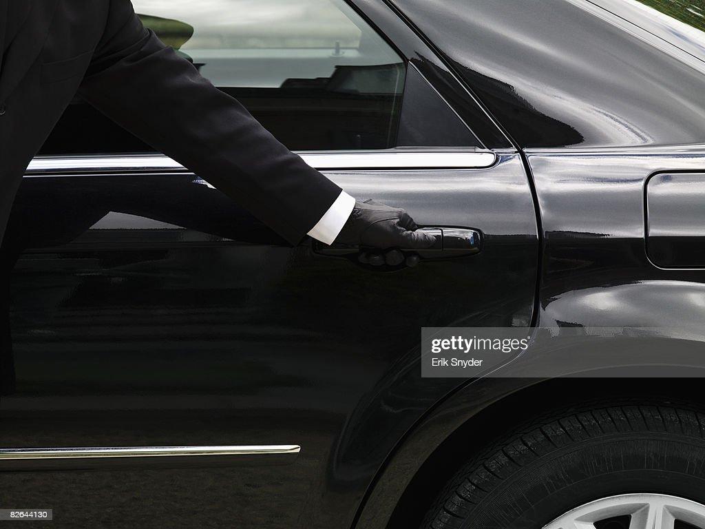 Chauffeur opening limousine door. : Stock Photo