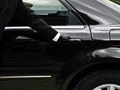 Chauffeur opening limousine door.