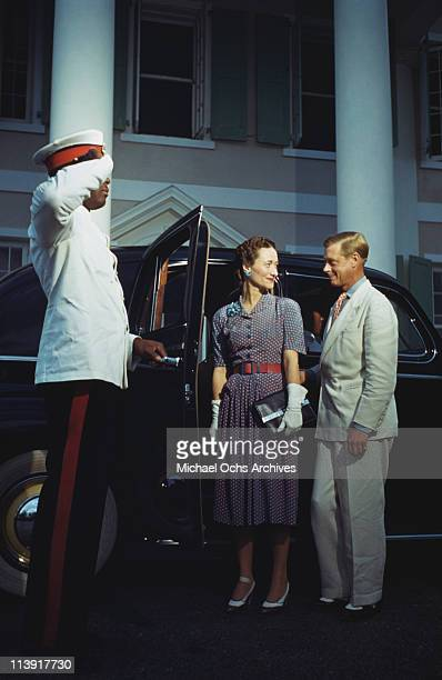 A chauffeur salutes as Wallis Duchess of Windsor and the Duke of Windsor get into a car outside Goverment House in Nassau the Bahamas circa 1942 The...