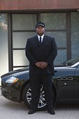 Chauffeur stands with hands clapsed at luxury vehicle