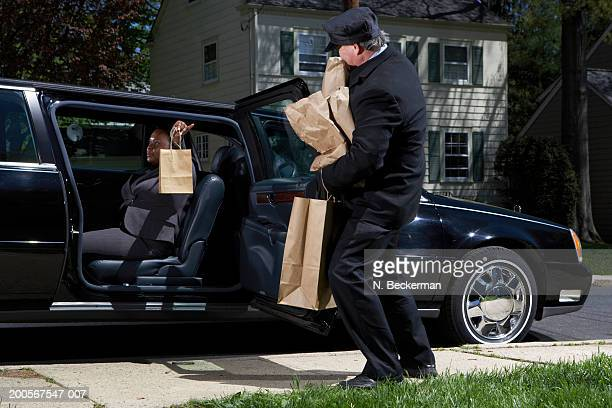 Chauffeur struggling with businesswoman's bags