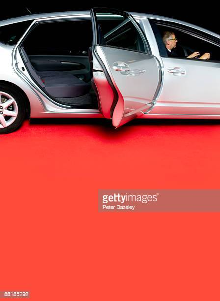 Chauffeur with stretched limo on red carpet.