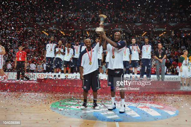 Chauncey Billups and Lamar Odom of the USA Senior Men's National Team hold up the trophy following the game against Turkey during the 2010 World...