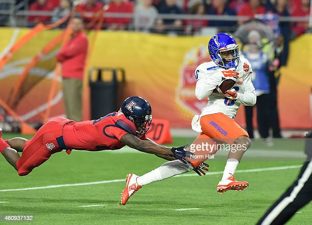 Chaz Anderson of the Boise State Broncos catches a 57 yard touchdown as Jarvis McCall Jr of the Arizona Wildcats attempts to make a diving tackle at...