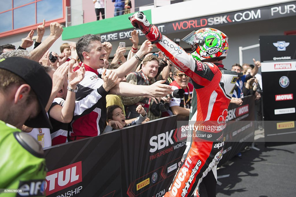 Chaz Davies of Great Britain and ARUBA.IT RACING-DUCATI celebrates the victory with team under the podium at the end of the Superbike Race 1 during the World Superbikes - Qualifying at Enzo & Dino Ferrari Circuit on April 30, 2016 in Imola, Italy.