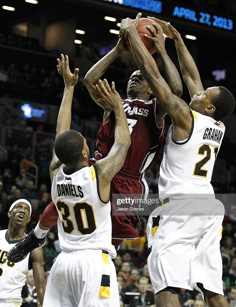 Chaz Williams #3 of the Massachusetts Minutemen is blocked as he goes up for a basket by Troy Daniels #30 and teammate Justin Tuoyo #31 of the Virginia Commonweath Rams in the second half during the Atlantic 10 Basketball Tournament - Semifinals at the Barclays Center on March 16, 2013 in the Brooklyn borough of New York City.