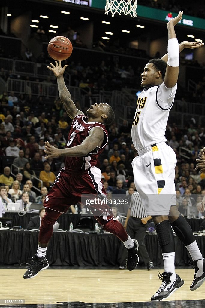 Chaz Williams #3 of the Massachusetts Minutemen puts up a basket past Justin Tuoyo #31 of the Virginia Commonweath Rams in the second half during the Atlantic 10 Basketball Tournament - Semifinals at the Barclays Center on March 16, 2013 in the Brooklyn borough of New York City.