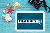 cheap flights searching, website page opened in digital tablet lying on turquoise table