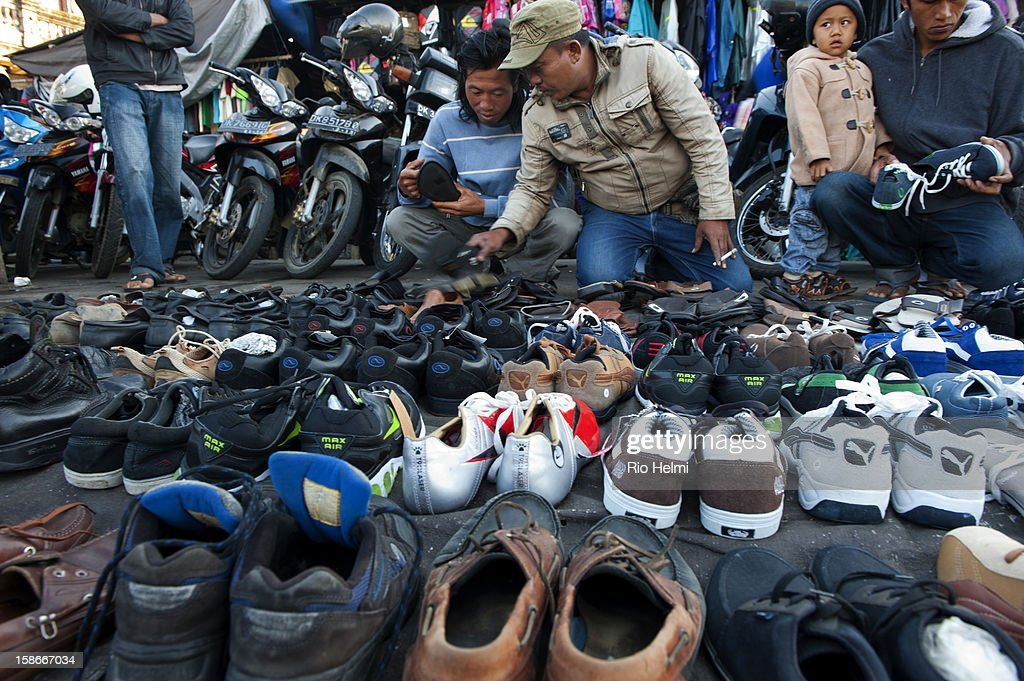 MARKET, KINTAMANI, BALI, INDONESIA - : Cheap shoes spread out on the ground get the attention of a potential buyer in the Kintamani market.