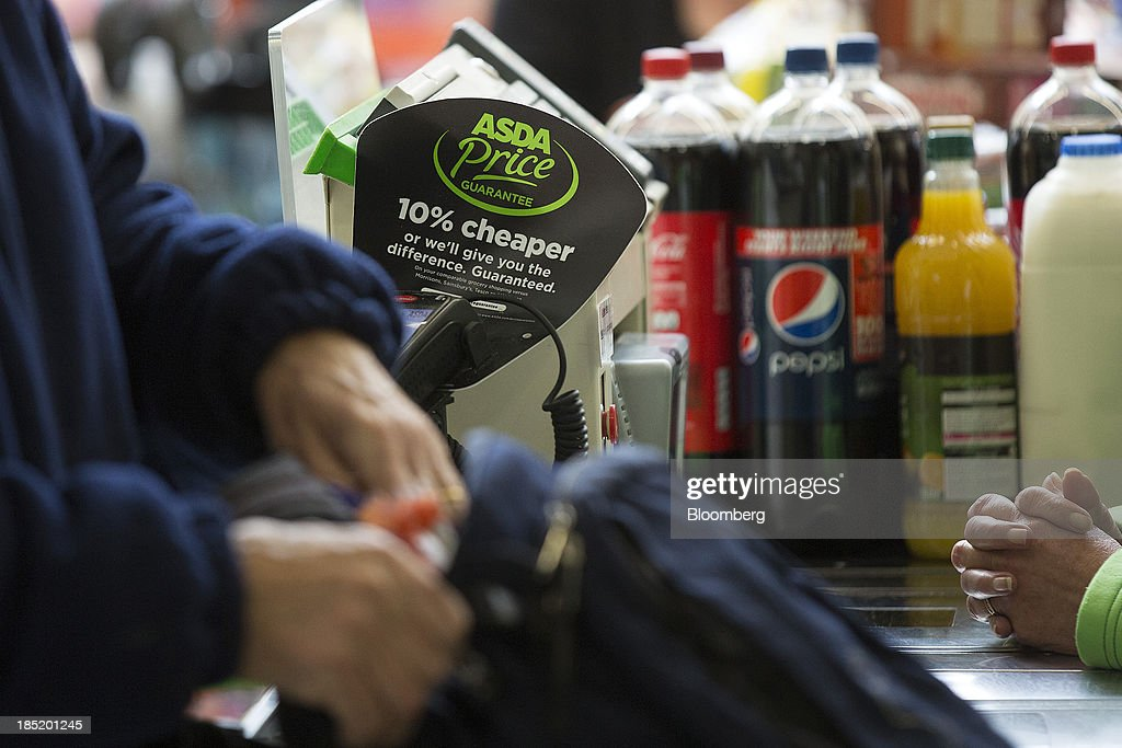 A '10% cheaper' label sits by a till as a customer prepares to pay for his shopping purchases at a check-out desk inside an Asda supermarket, the U.K. retail arm of Wal-Mart Stores Inc., in Watford, U.K., on Thursday, Oct. 17, 2013. U.K. retail sales rose more than economists forecast in September as an increase in furniture demand led a rebound from a slump the previous month. Photographer: Simon Dawson/Bloomberg via Getty Images
