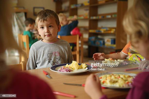 Chechen child Ayshat Musayeva sits down for lunch at the local kindergarten she and her siblings attend on October 9 2015 in Letschin Germany The...