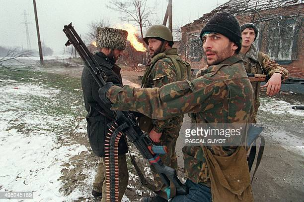 A Chechen fighter checks his weapon while chatting with some comrades on January 17 1995 on the outskirts of Grosny in the breakaway Republic of...