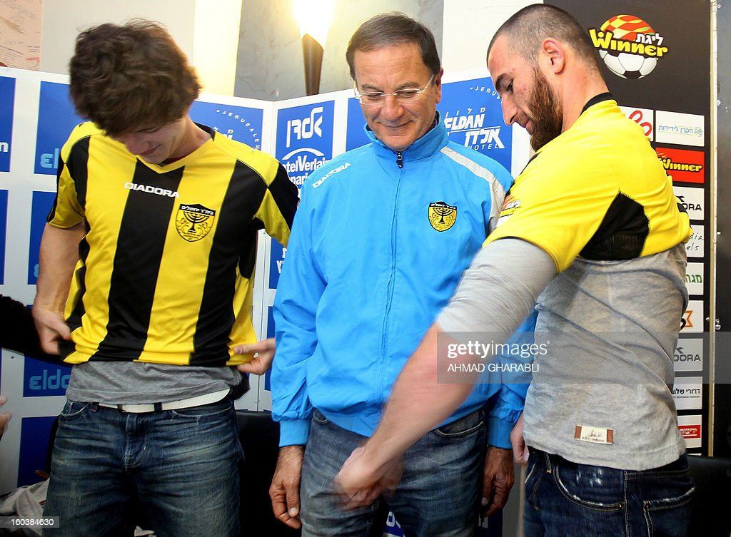 Chechen football players Dzhabrail Kadaev (L) and Zaur Sadaev (R) are watched by their new coach Eli Cohen as they try on their shirts during their introduction by the Beitar Jerusalem football club to the press in Jerusalem on January 30, 2013. Beitar Jerusalem, owned by Russian-Israeli Arkady Gaydamak, is in turmoil after some fans lashed out at the owner's plan to sign the two Muslim players, insisting the club would remain 'pure' and causing uproar during a weekend game.