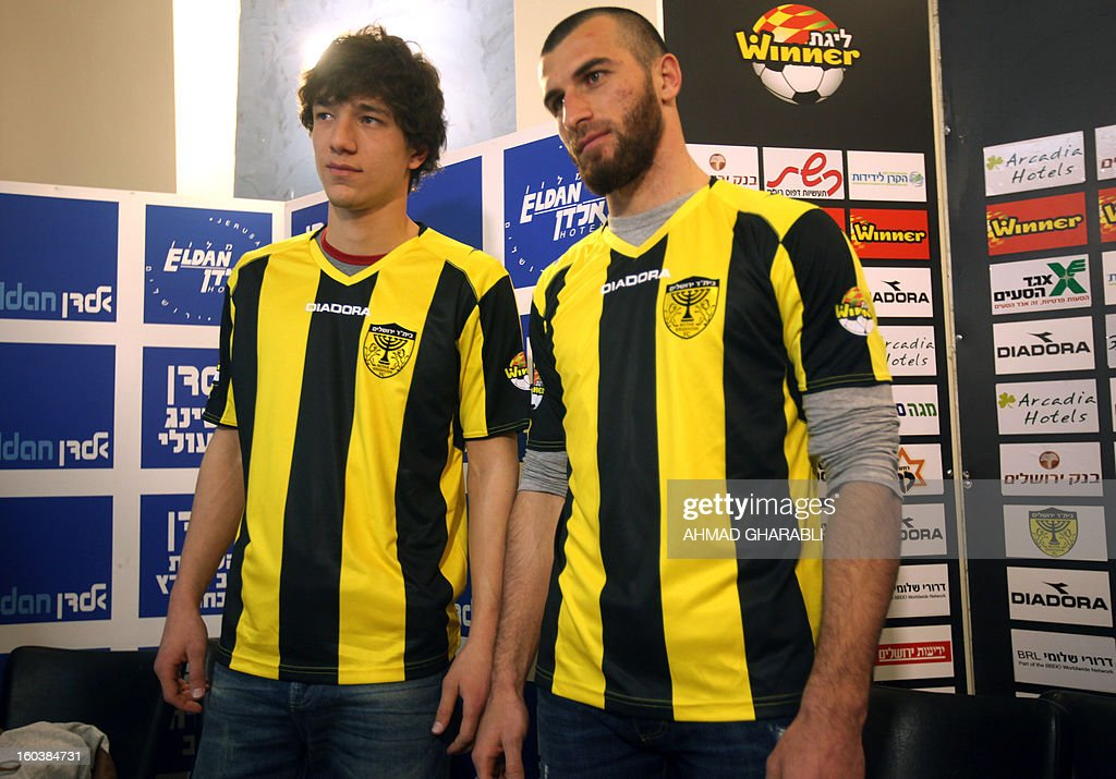 Chechen football players Dzhabrail Kadaev (L) and Zaur Sadaev, signed from Russian League club Terek Grozny, show off their new shirts during their introduction by the Beitar Jerusalem football club to the press in Jerusalem on January 30, 2013. Beitar Jerusalem, owned by Russian-Israeli Arkady Gaydamak, is in turmoil after some fans lashed out at the owner's plan to sign the two Muslim players, insisting the club would remain 'pure' and causing uproar during a weekend game.