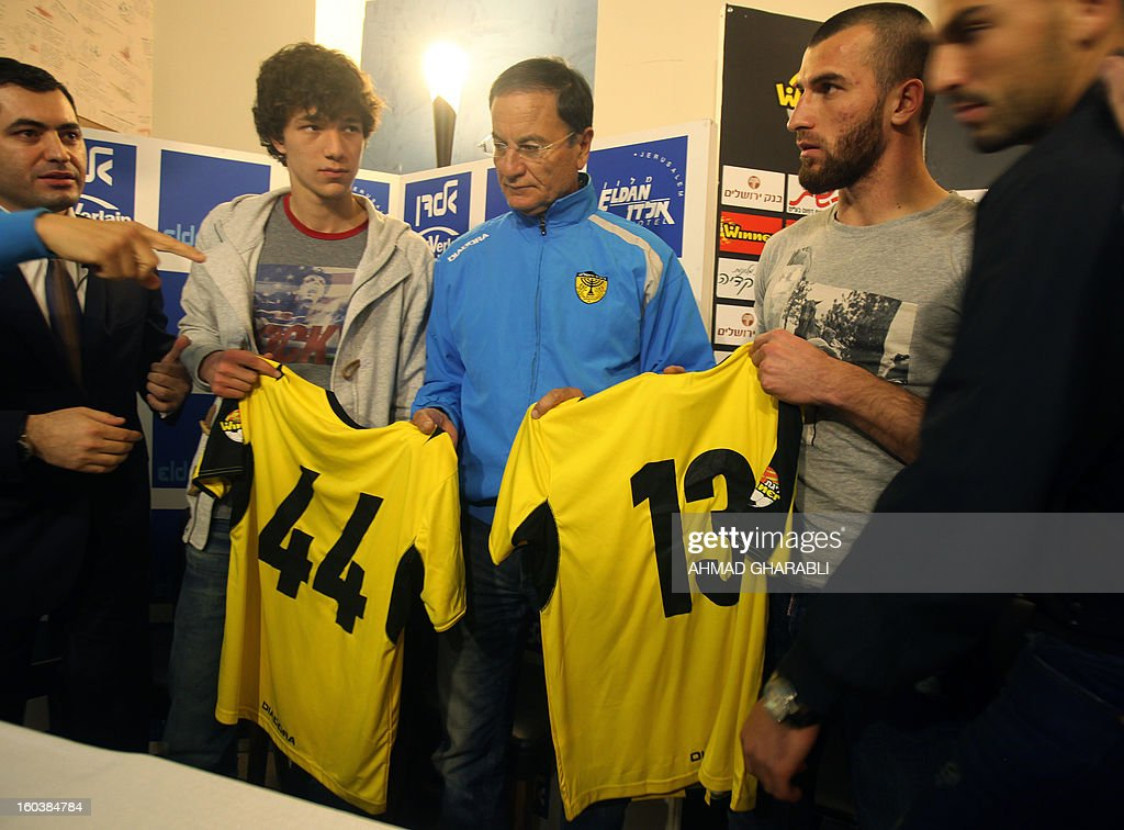 Chechen football players Gabriel Kadiev (L) and Zaur Sadayev (R) are watched by their new coach Eli Cohen as they hold their shirts during their introduction by the Beitar Jerusalem football club to the press in Jerusalem on January 30, 2013. Beitar Jerusalem, owned by Russian-Israeli Arkady Gaydamak, is in turmoil after some fans lashed out at the owner's plan to sign the two Muslim players, insisting the club would remain 'pure' and causing uproar during a weekend game.
