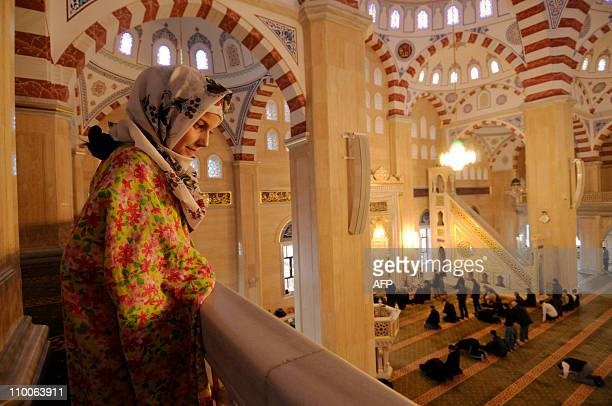 Chechen girl Madina looks at worshippers in Akhmad Kadyrov Central Dome Mosque known as 'Heart of Chechnya' in the Chechnya's provincial capital...