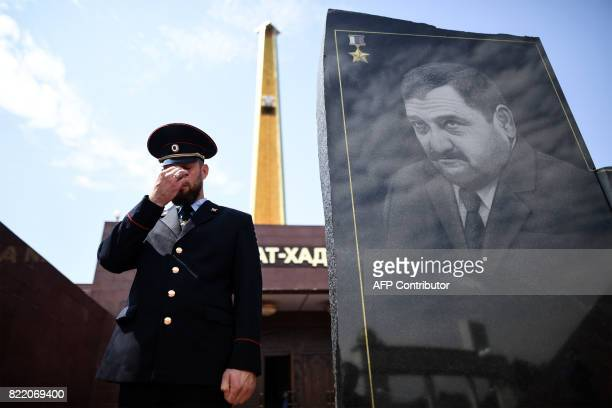 A Chechen police officer gestures as he stands guard in front of the memorial for Akhmad Kadyrov the father of current Chechen President Ramzan...