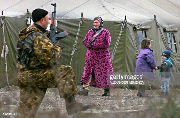 Chechen woman passes by a Russian officer in a refugee camp in the village of Znamenskoye northern Chechnya 23 November 2000 Members of a commission...