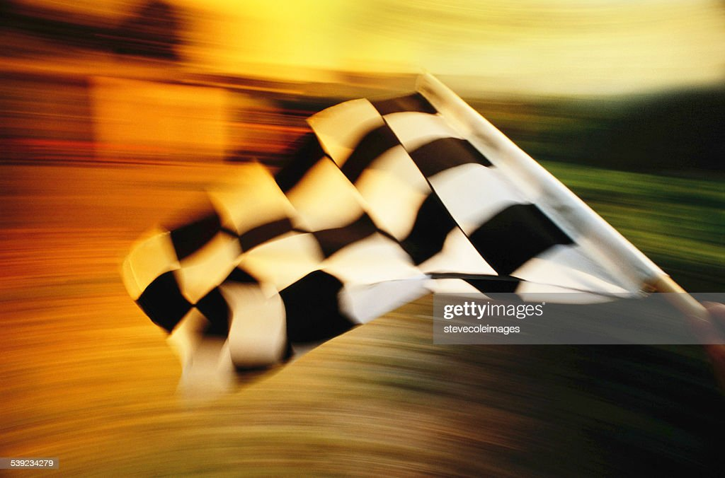 Checkered flag waving at an car race. : Stock Photo