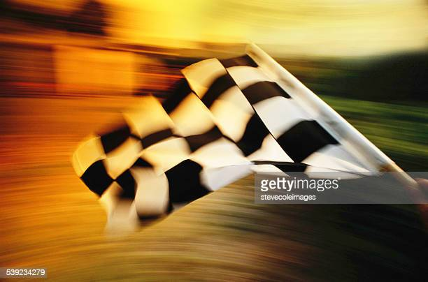 Checkered flag waving at an car race.