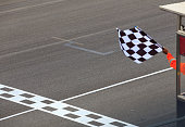 A checkered flag waving at an car race. Waving check flag in air at race finish, motion blur on flag.