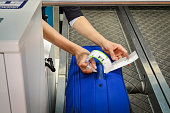 check-in employee attaches a luggage tag to suitcase of passenger - close up of hands