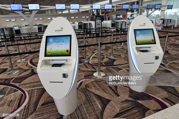Checkin kiosks are seen past automated bagdrop counters during a media preview at the departure hall of Changi Airport's newlybuilt Terminal 4 in...
