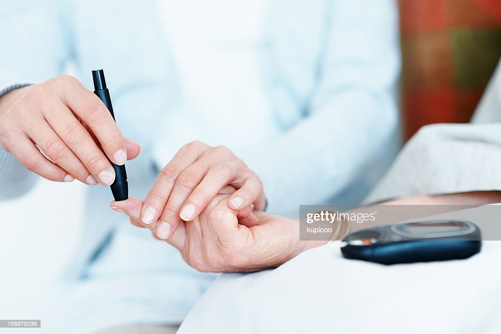 Checking her blood-sugar levels : Stock Photo