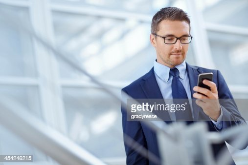 Checking his emails thanks to smartphone technology : Stock Photo