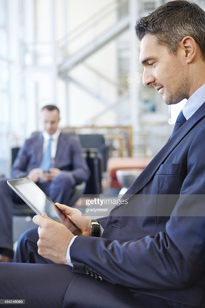 Checking his emails while he waits : Stock Photo