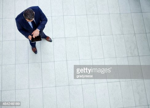 Checking his tablet : Stock Photo
