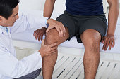 Doctor checking knee joint of male sportsman