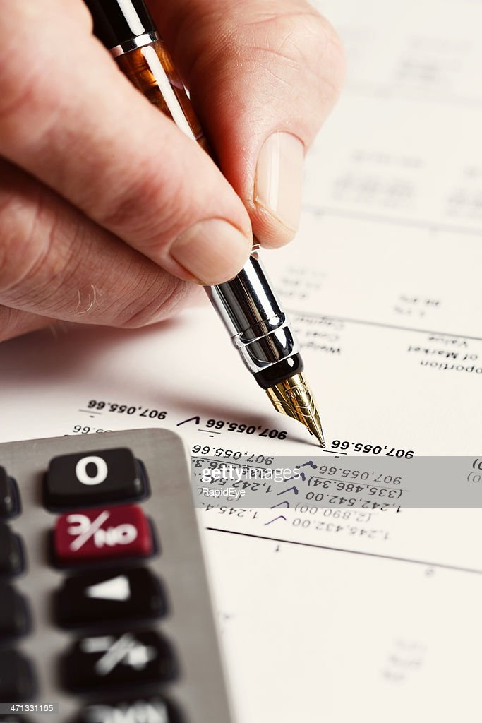 Checking off items with pen and calculator on financial printout