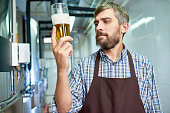 Waist-up portrait of bearded middle-aged brewer wearing checked shirt and apron tasting fresh beer while standing at modern beer factory