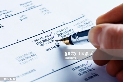 Checking the finances; man's hand marks off spreadsheet figures