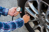 Checking tire pressure with pressure gauge