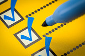 Yellow Checklist with Blue Marker Close Up.