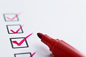 Checklist with check mark and red pen.