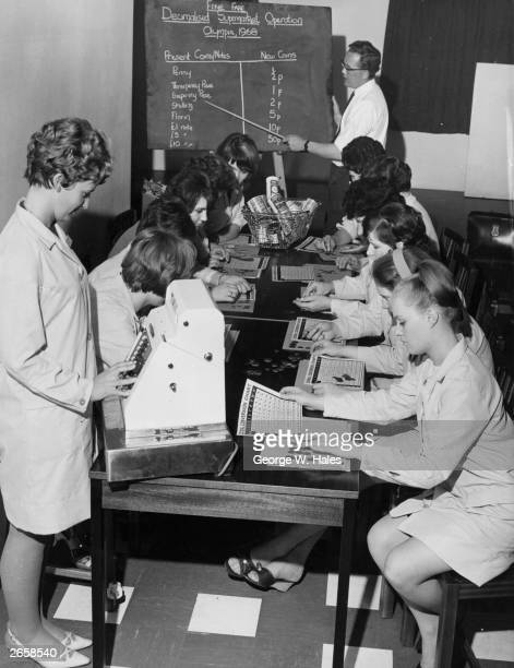 Checkout workers at a Fine Fare supermarket studying decimal conversion charts during a training course