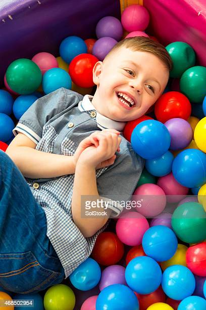 Cheeky little boy playing in a ball pit
